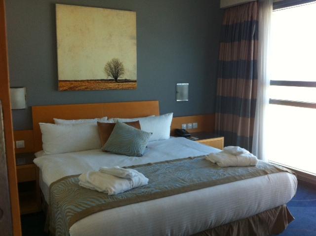 המיטה נוחה ורחבה, החדר מעוצב, הקיר שקוף ונפתח אל החוף, הים ובתי העיר.